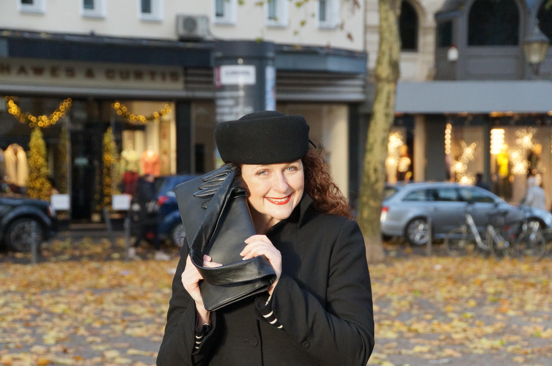 Ü40 Bloggerin Cerstin aus Köln mit einer Maison Martin Margiela Glove Clutch, Pillboxhut und Mantel von Annette Görtz über drei Stilwörter für den Modeblog iknmlo